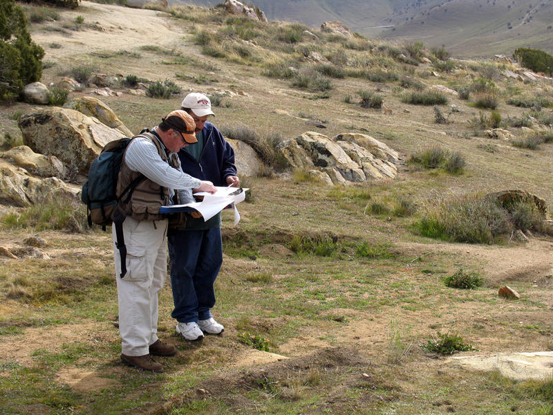 Two site stewards write their observations on a CASSP site visit form at a prehistoric site in the Sierras.