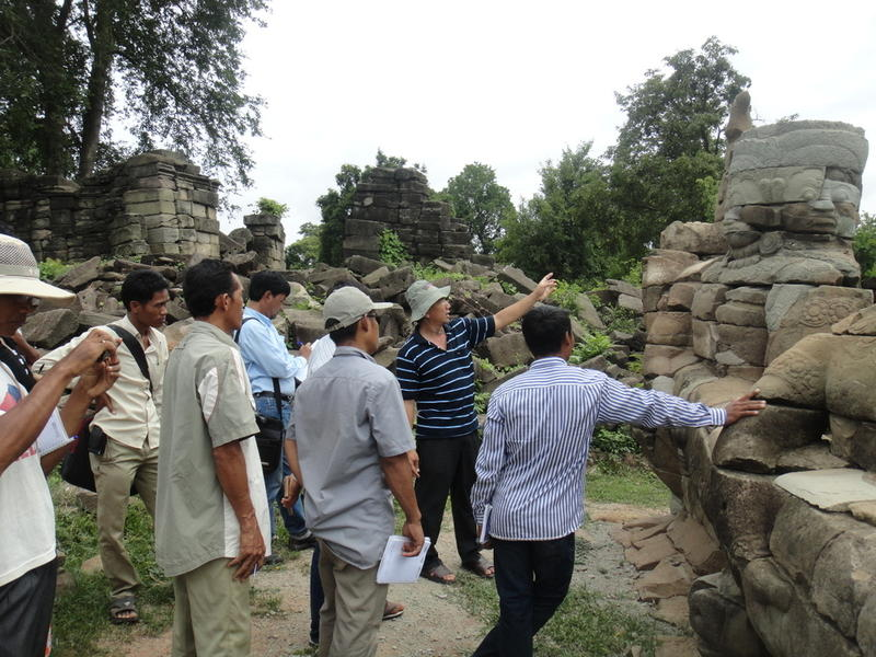A resource employee explains efforts to restore a statue at the South causeway of Banteay Chhmar